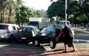 Người đi xe đạp tay không nhấc bổng ô tô chắn đường