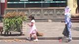 Bé gái đầu trần giúp mẹ quét rác dưới trời nóng 40 độ