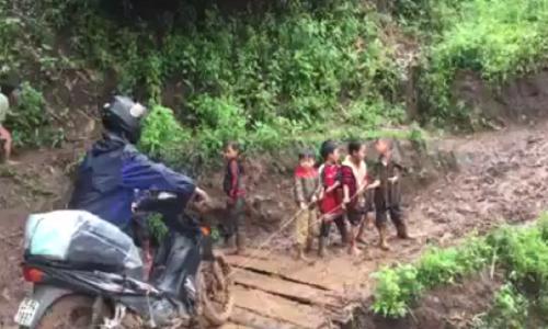 Hoc sinh lop 1 keo xe cho thay qua doan duong kho